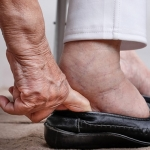 An older woman with swollen feet puts on her shoes.