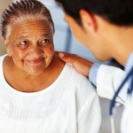 older woman with doctor's hand on her shoulder
