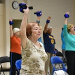 An older woman exercises with a hand weight in a class