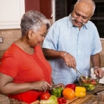 older woman and man cooking with vegetables