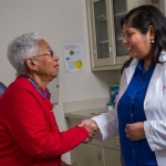 Older woman greets her doctor in the doctor's office