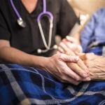 Nurse holding elderly woman's hands