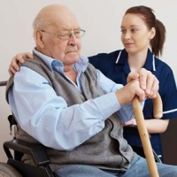 Older man in a wheelchair with a nurse
