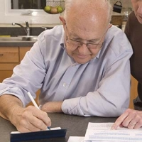 Older man with Alzheimer's writes checks while caregiver supervises