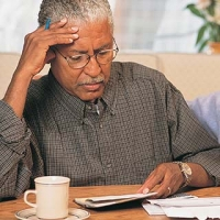 Older man filling out legal and financial paperwork for people with Alzheimer's disease