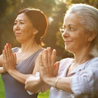 2 older women doing yoga meditation