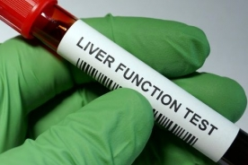 gloved hand of medical professional holding a liver function test blood vile