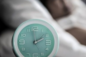 alarm clock near a woman having trouble sleeping