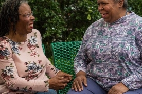 two African American women talking on a bench outside