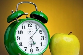 green alarm clock with an apple