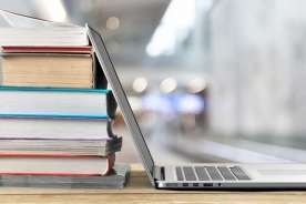 A stack of books on a table with an open laptop resting against the books