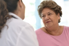 Older Hispanic woman talking with a doctor