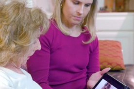 An older woman engages in a video consult with her doctor using a wireless tablet as her daughter listens.