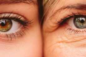 Close up on eyes of mother and daughter with faces next to one another.