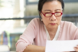 Older Asian woman with dementia reviewing her finances.