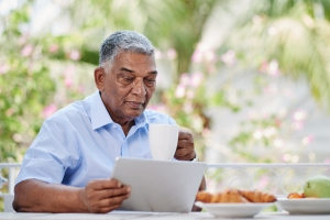 Older man reading NIA news about Alzheimer's and related dementias on a tablet