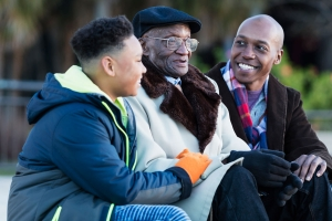 Older man with dementia talking to his son and grandson