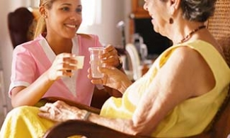 Older woman with Alzheimer's in a care facility with a caregiver
