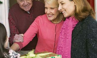Older adults welcoming family with holiday presents