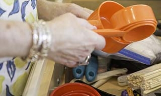 older person rummaging through a kitchen drawer