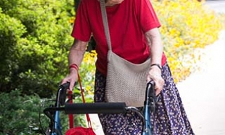 Older woman using a walker on a sidewalk