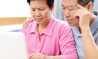 Asian couple looking at cognitive health resources on a computer