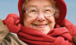 Older woman wearing tan coat and red hat, scarf and gloves