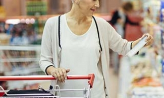 Older woman checking prices on groceries