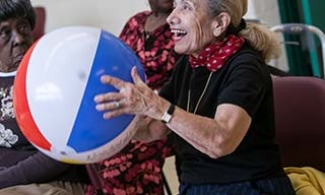 Group of older adults playing seated volleyball with a beach ball