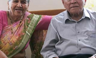 Indian couple sitting on a sofa.