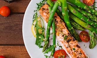 Plate of salmon, tomatoes, asparagus, lemon and herbs