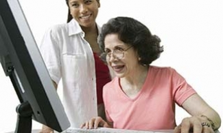 Older woman looking at clinical trials information online with her doctor