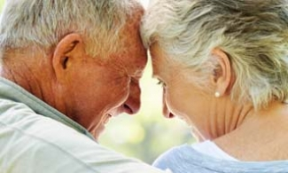 Older couple hugging on a bench