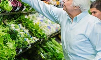 Older man choosing leafy green vegetables at the grocery store