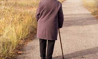 Older woman wandering alone down a rural road