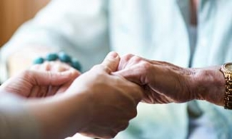 Caregiver holding an older woman's hands.