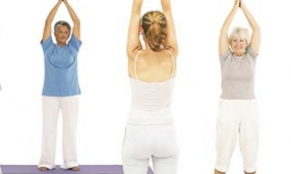 2 older adults following a yoga teacher's instructions