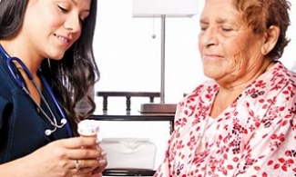 Older woman listening to nurse talk about medications