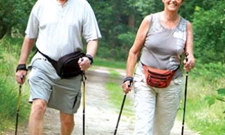 Older couple hiking with walking poles