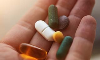 Variety of vitamins in a person's hand.