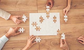 People working together to put missing pieces into a puzzle.