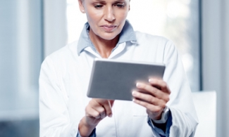 woman in a lab coat using a tablet