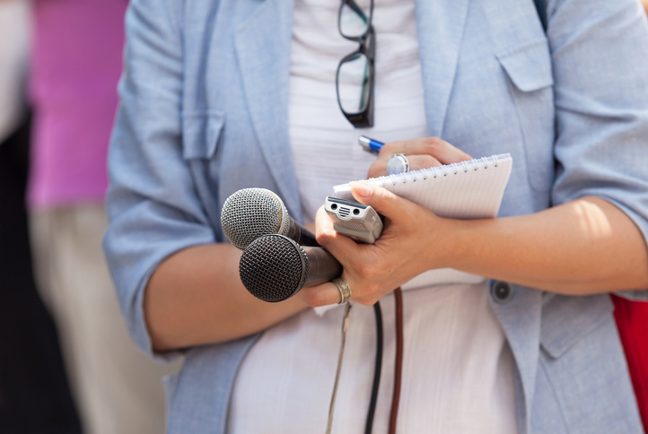 Reporter is holding microphones, tape-recorder and notepad